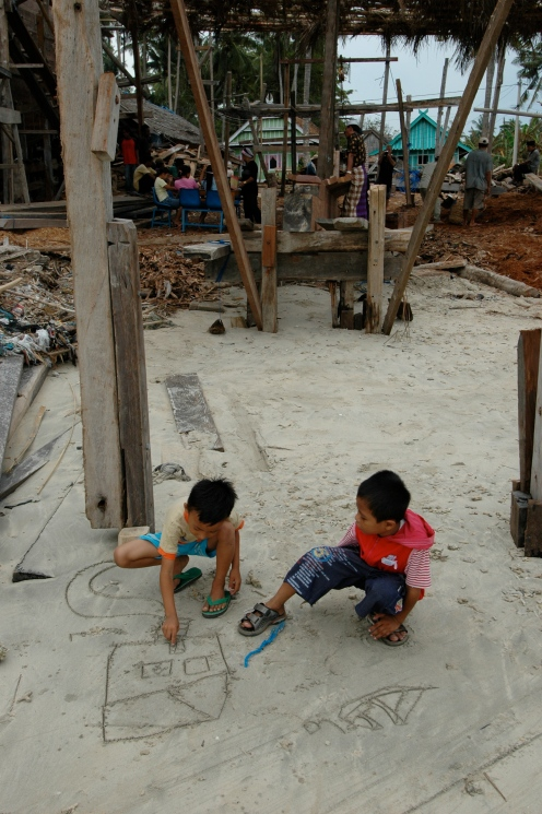 Children play in the sand under the timbers of the vessels being constructed.